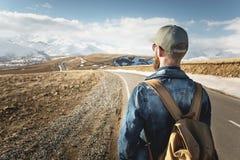 Ένα γενειοφόρο άτομο σε μια ΚΑΠ με ένα σακίδιο πλάτης έτοιμο να προχωρήσει αρκετά Ένα άτομο σε μια εθνική οδό ενάντια στο σκηνικό Στοκ φωτογραφία με δικαίωμα ελεύθερης χρήσης