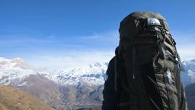 Ένα γενειοφόρο άτομο στο καπέλο γυαλιών ηλίου με ένα σακίδιο πλάτης και μια κάμερα στέκεται υψηλό στα βουνά και κοιτάζει στα περι απόθεμα βίντεο