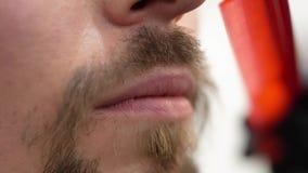Ένα γενειοφόρο hipster κτενίζει ένα mustache με μια χτένα απόθεμα βίντεο
