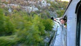 Ένα γενναίο νέο κορίτσι κλίνει έξω το κινούμενο τραίνο παραθύρων γρήγορα που πλησιάζει τη σήραγγα Γελά και ευτυχές ταξίδι στοκ εικόνα