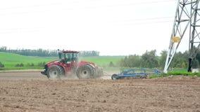 Ένα γεωργικό τρακτέρ που οργώνει έναν τομέα Λόφοι και ένα δάσος στο υπόβαθρο απόθεμα βίντεο