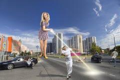 Ένα γιγαντιαίο κορίτσι καίει ένα άτομο από έναν καθρέφτη με το απεικονισμένο φως του ήλιου στοκ φωτογραφία με δικαίωμα ελεύθερης χρήσης