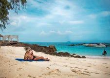 Ένα γκρίζος-μαλλιαρό άτομο με μακρυμάλλη στην παραλία Βρίσκεται στην άμμο, πίνει τον καφέ, καπνίζει ένα τσιγάρο και εξετάζει την  Στοκ εικόνες με δικαίωμα ελεύθερης χρήσης
