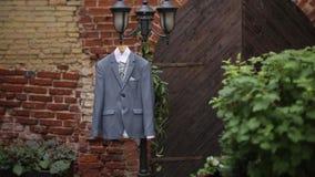 Ένα γκρίζο κοστούμι σακακιών ατόμων ` s που κρεμά στο ναυπηγείο κρεμά σε μια κρεμάστρα πριν από το γάμο νεόνυμφων ` s φιλμ μικρού μήκους