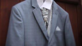 Ένα γκρίζο κοστούμι σακακιών ατόμων ` s που κρεμά στο ναυπηγείο κρεμά σε μια κρεμάστρα πριν από το γάμο νεόνυμφων ` s απόθεμα βίντεο