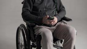 Ένα γκρίζο μαλλιαρό άτομο σε μια αναπηρική καρέκλα ακούει την αγαπημένη μουσική με τα ακουστικά απόθεμα βίντεο