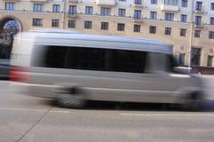 Ένα γκρίζο μικρό λεωφορείο κάτω με μια θαμπάδα στην κίνηση Στοκ Εικόνες