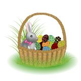Ένα γκρίζο χαριτωμένο κουνέλι κάθεται σε ένα καλάθι με τα χρωματισμένα αυγά Πάσχας Το σύμβολο Πάσχας στον πολιτισμό πολλών χωρών  διανυσματική απεικόνιση