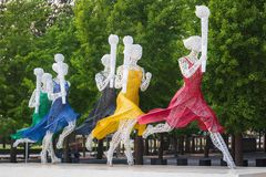 Ένα γλυπτό των τρέχοντας γυναικών με τους ολυμπιακούς φανούς στοκ εικόνα