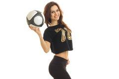 Ένα γοητευτικό νέο αθλητικό κορίτσι στέκεται λοξά τα χαμόγελα και αύξησε τη σφαίρα υπό εξέταση Στοκ Φωτογραφία