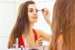 Ένα γοητευτικό νέο κορίτσι σε ένα κόκκινο πουκάμισο στέκεται μπροστά από έναν καθρέφτη και ένα μάτι μελανιού χρώματος Στοκ Εικόνες