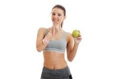 Ένα γοητευτικό νέο κορίτσι τρώει την πράσινα Apple και ένα χαμόγελο Στοκ Εικόνες