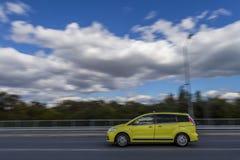 Ένα γρήγορα κινούμενο αυτοκίνητο ενάντια στο σκηνικό ενός όμορφου μπλε ουρανού και χνουδωτών άσπρων σύννεφων στοκ φωτογραφίες με δικαίωμα ελεύθερης χρήσης