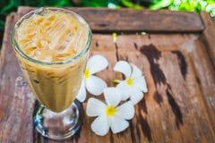 Ένα γυαλί καφέ στον κήπο με το άσπρο plumeria ανθίζει στο ξύλο Στοκ Εικόνα