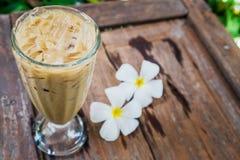 Ένα γυαλί καφέ στον κήπο με το άσπρο plumeria ανθίζει στο ξύλο Στοκ Φωτογραφίες