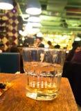 Ένα γυαλί ουίσκυ στον πίνακα με το μπαρ στο υπόβαθρο Στοκ Εικόνες
