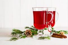 Ένα γυαλί του κοκκίνου - καυτό θερμαμένο κρασί σε ένα ελαφρύ υπόβαθρο Χριστούγεννα καρτών που χ&a Στοκ Εικόνες