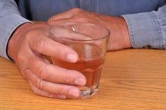 Ένα γυαλί του οινοπνεύματος στο χέρι του στοκ φωτογραφίες