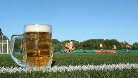 Ένα γυαλί των στάσεων μπύρας στην πράσινη χλόη σε έναν αγωνιστικό χώρο ποδοσφαίρου, φορείς παίζει το ποδόσφαιρο απόθεμα βίντεο
