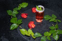 Ένα γυαλί ψεκάζεται με τη ζάχαρη, υπάρχει tincture φραουλών μέσα, ένα κλαδάκι της μέντας στην κορυφή σε ένα σκοτεινό κλίμα στοκ φωτογραφία