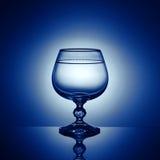 Ένα γυαλί κρασιού σε ένα μπλε υπόβαθρο Στοκ εικόνα με δικαίωμα ελεύθερης χρήσης