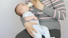 Ένα δίμηνο νεογέννητο μωρό βρίσκεται στα όπλα μητέρων και απορροφά μια θηλή από το μπουκάλι του γάλακτος απόθεμα βίντεο