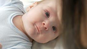 Ένα δίμηνο παλαιό ευτυχές νεογέννητο μωρό βρίσκεται στο κρεβάτι και δοκιμάζει τις συγκινήσεις στη μητέρα του Ένα μωρό γελά, μιλά, απόθεμα βίντεο