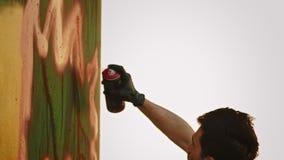 Ένα δημιουργικό όμορφο άτομο με μια δερματοστιξία που χρωματίζει τον τοίχο με ένα χρώμα αερολύματος φιλμ μικρού μήκους