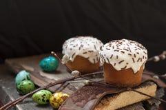 Ένα δύο μικρό Πάσχα κέικ και βαμμένα αυγά ορτυκιών, και ένας κλαδίσκος ιτιών σε ένα σκοτεινό ξύλινο υπόβαθρο Στοκ εικόνες με δικαίωμα ελεύθερης χρήσης