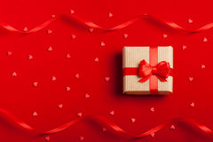 Ένα δώρο σε ένα κιβώτιο σε ένα κόκκινο υπόβαθρο Στοκ Εικόνες