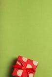 Ένα δώρο σε ένα κιβώτιο σε ένα υπόβαθρο πρασινάδων Στοκ Φωτογραφίες