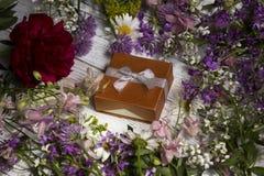Ένα δώρο σε ένα κουτί από χαρτόνι, γύρω από πολλά ρόδινα, ιώδη και κόκκινα λουλούδια Στοκ Εικόνα