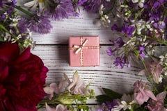 Ένα δώρο σε ένα ρόδινο κιβώτιο χαρτονιού, γύρω από πολλά ρόδινα, ιώδη και κόκκινα λουλούδια Στοκ Εικόνα