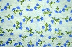 Ένα δείγμα του υφάσματος: η σύσταση και τα μπλε λουλούδια Στοκ Εικόνα