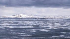 Ένα λείο φύλλο του κρύου ωκεάνιου νερού με τα σκοτεινά σύννεφα ανωτέρω Στοκ Εικόνες