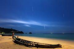 Ένα εγκαταλειμμένο ξύλινο αλιευτικό σκάφος σε μια παραλία άμμου τη νύχτα Στοκ Εικόνες