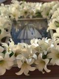 Ένα εικονίδιο της Virgin Mary κρεμά έξω σε μια εκκλησία που περιβάλλεται από τα πλαστικά λουλούδια Στοκ εικόνα με δικαίωμα ελεύθερης χρήσης