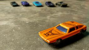 Ένα εκλεκτικό παιχνίδι αυτοκινήτων Κινηματογράφηση σε πρώτο πλάνο του πορτοκαλιού αυτοκινήτου παιχνιδιών για τα παιδιά στο διαφορ στοκ φωτογραφία με δικαίωμα ελεύθερης χρήσης