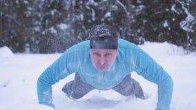 Ένα εκφραστικό άτομο που ωθεί επάνω στο χιόνι σε ένα χειμερινό δάσος απόθεμα βίντεο
