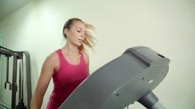 Ένα ελκυστικό κορίτσι εργάζεται treadmill στη γυμναστική φιλμ μικρού μήκους