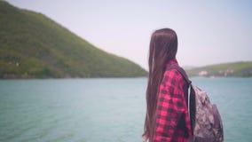 Ένα ελκυστικό κορίτσι σε ένα κόκκινο πουκάμισο καρό, που θέτει για τη κάμερα Το κορίτσι πηγαίνει κατά μήκος της ακτής της λίμνης  φιλμ μικρού μήκους