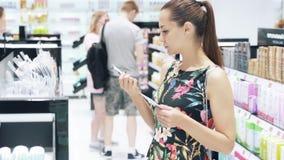 Ένα ελκυστικό νέο κορίτσι σε ένα φόρεμα επιλέγει στα καλλυντικά καταστημάτων για το πρόσωπο, διαβάζει τις επιγραφές στα μπουκάλια απόθεμα βίντεο