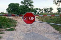 Ένα εμπόδιο με ένα οδικό σημάδι εμποδίζει το δρόμο και απαγορεύει τη μετάβαση στοκ φωτογραφία