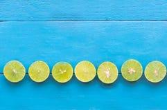 ένα λεμόνι ασβέστη είναι μισή περικοπή και τακτοποιεί στη στήλη στο μπλε ξύλινο β Στοκ Φωτογραφίες