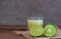 ένα λεμόνι και ένας χυμός ασβέστη στο διαφανές γυαλί με το ύφασμα σάκων στο ρ Στοκ εικόνες με δικαίωμα ελεύθερης χρήσης