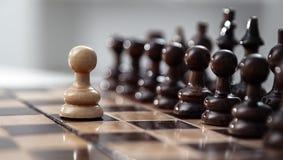 Ένα ενέχυρο που μένει ενάντια στο πλήρες σύνολο κομματιών σκακιού Στοκ Φωτογραφία