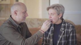 Ένα ενήλικο άτομο θεραπεύει την ώριμη σύζυγό του με έναν φραγμό σοκολάτας καθμένος σε έναν καναπέ σε ένα δωμάτιο Οικογενειακές σχ φιλμ μικρού μήκους