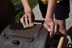 Ένα ενήλικο άτομο που καθαρίζει την υπαίθρια σχάρα στοκ φωτογραφία με δικαίωμα ελεύθερης χρήσης