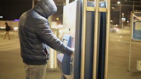 Ένα ενήλικο άτομο σε ένα θερμό σακάκι χρησιμοποιεί την οθόνη αφής της μηχανής χώρων στάθμευσης για να πληρώσει για το χώρο στάθμε απόθεμα βίντεο