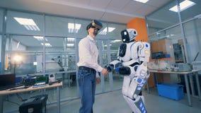 Ένα ενήλικο άτομο στα εικονικά γυαλιά τινάζει το χέρι ρομπότ ` s και γυρίζει γύρω φιλμ μικρού μήκους